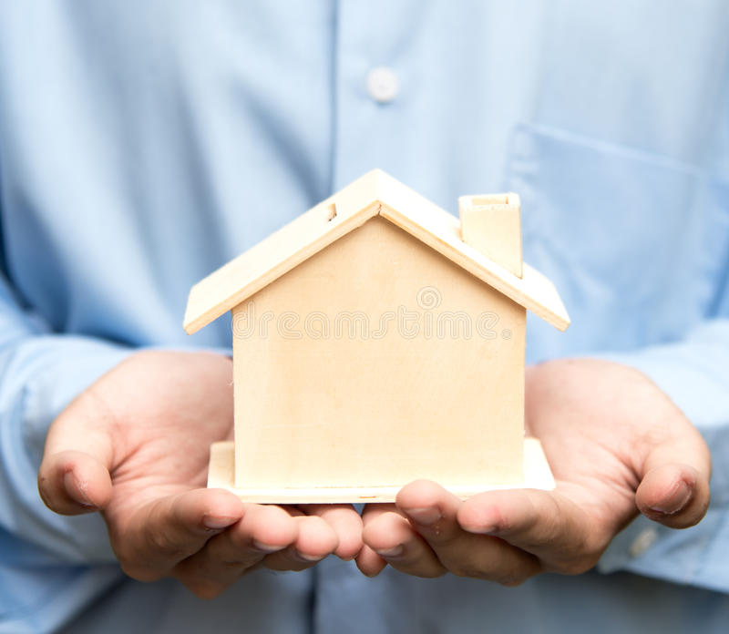 Человек держа дом представляя владение недвижимостью стоковая фотография