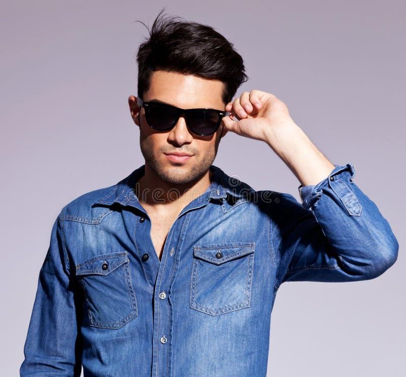 Человек держа его модные солнечные очки стоковая фотография