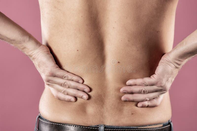Человек держа его тягостную воспламененную поясницу на розовой предпосылке Здравоохранение и микстура Страдать от боли в спине стоковое изображение rf