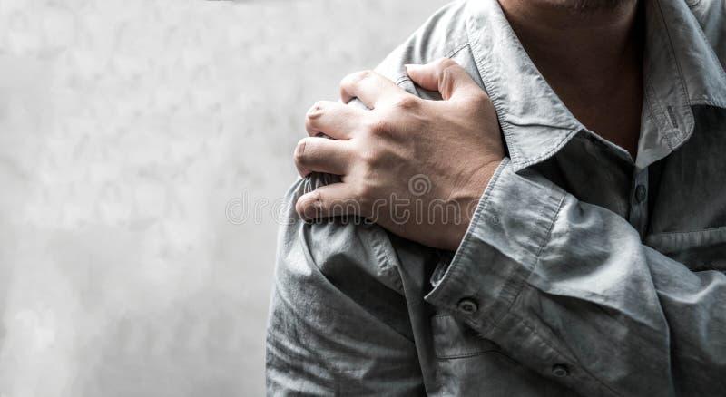 Человек держа его тягостные плечо, здравоохранение и боль в человеческом теле стоковое изображение