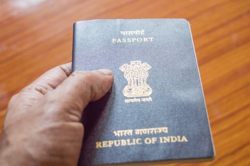 Человек держа индийскую книгу паспорта над предпосылкой паркета деревянного стола, выборочным фокусом конец вверх Туризм перемеще стоковые фотографии rf