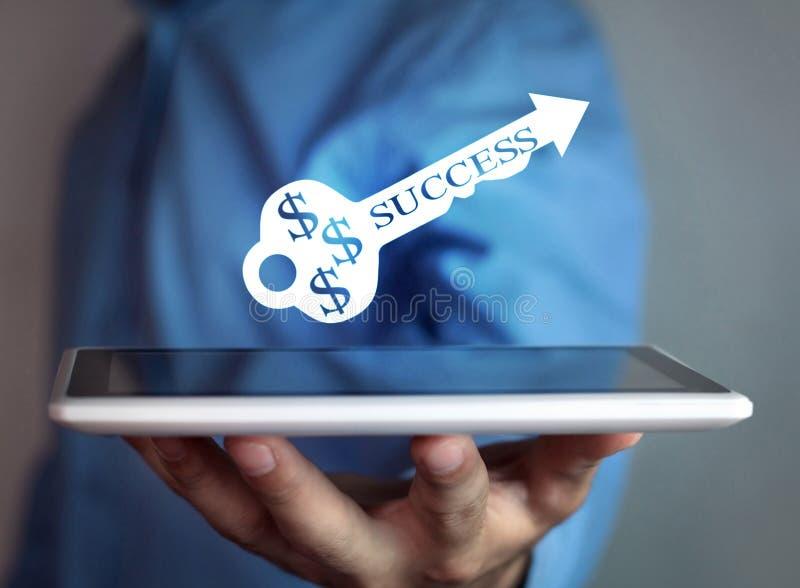 Человек держа ключ успеха стоковое изображение