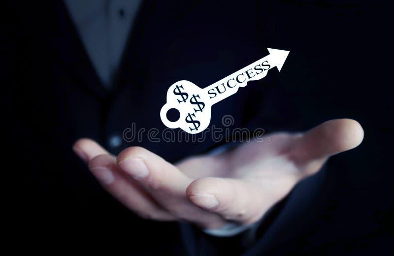 Человек держа ключ успеха стоковые изображения