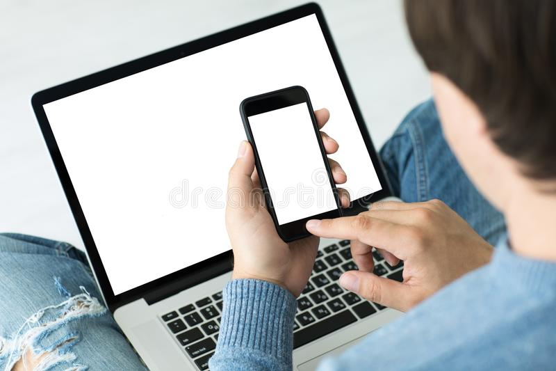 Человек держа компьтер-книжку и телефон с изолированным экраном