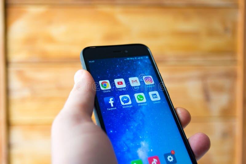 Человек держа конец сотового телефона вверх с известными социальными приложениями средств массовой информации на экране стоковые фото