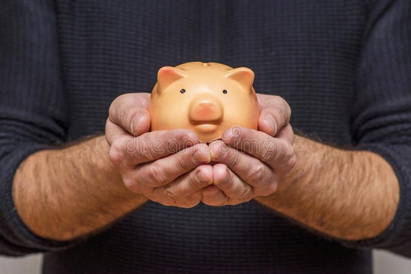 Человек держа копилку Человек держа копилку в его символе рук сбережений и хороших инвестиций стоковая фотография