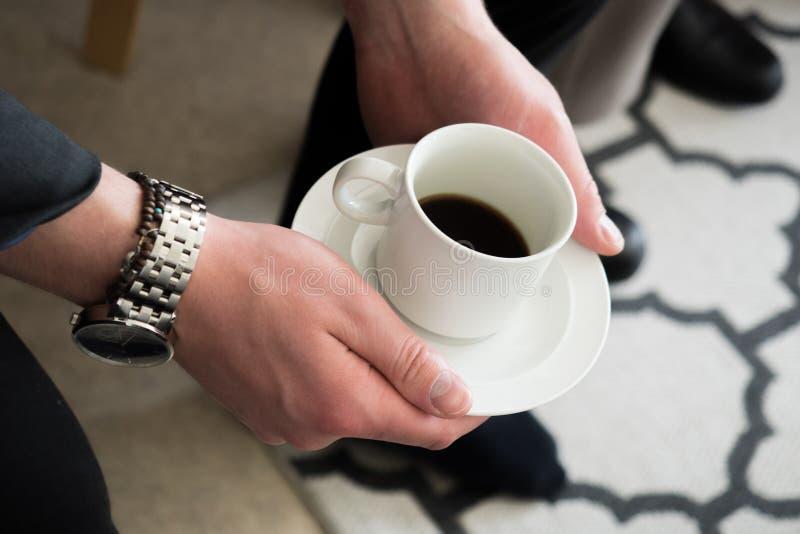 Человек держа кофейную чашку в руках стоковое изображение rf