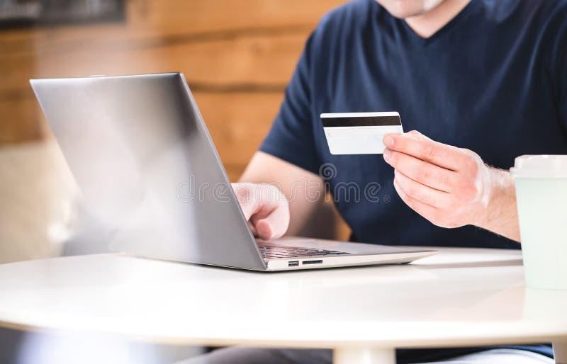 Человек держа кредитную карточку и печатая данные по банка стоковые изображения rf