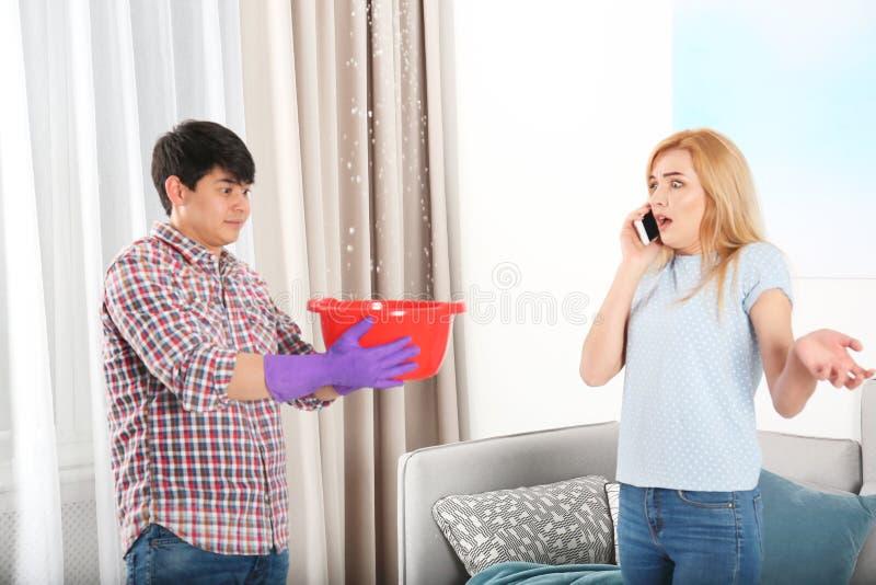 Человек держа пластиковый таз под утечкой воды от потолка пока женщина вызывая водопроводчика стоковая фотография rf