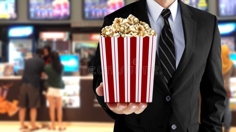 Человек держа попкорн на счетчике кино стоковая фотография rf