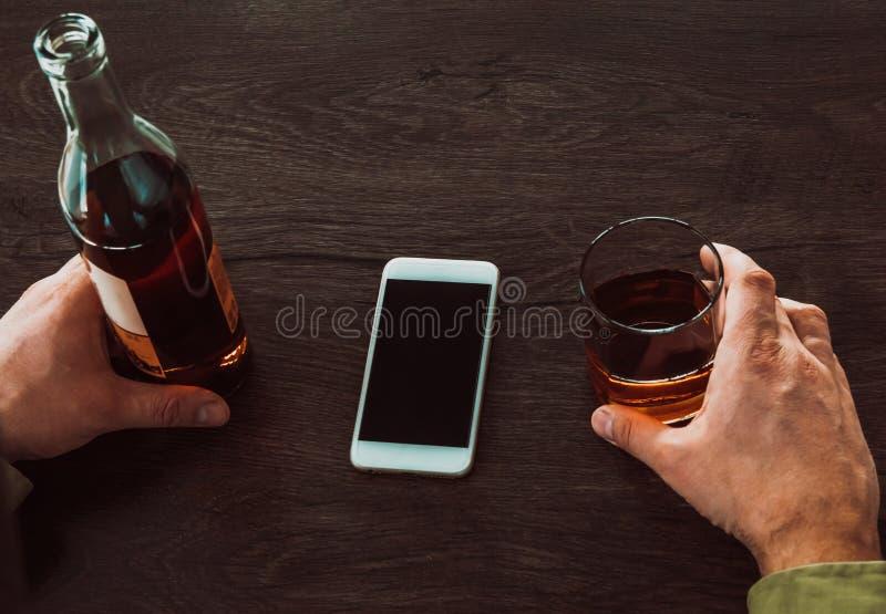 Человек держа стекло вискиа и бутылки алкоголя, на таблице мобильный телефон стоковые изображения