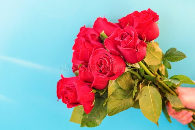 Человек держит букет красивых красных роз на голубой предпосылке, конца-вверх Международный женский день, день рождения, День мат стоковое изображение rf