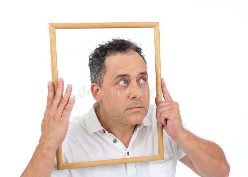 Человек держит деревянную рамку Он полон и носит a стоковое фото