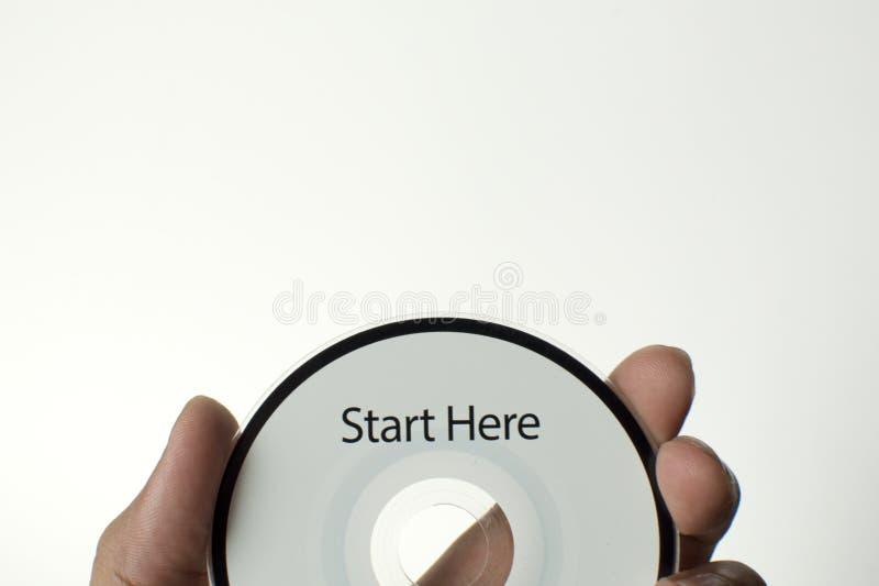 Человек держит компактный диск с сообщением старта здесь стоковые изображения