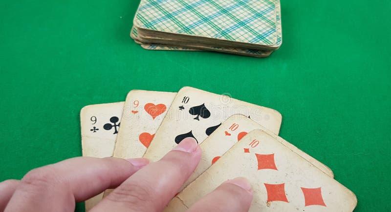 Человек держит пальцы на 5 игральных картах стоковые изображения rf