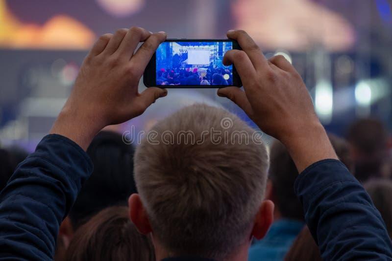 Человек держит смартфон в его руках и показателях или передает концерт в реальном маштабе времени улицы среди толпы вентиляторов  стоковая фотография