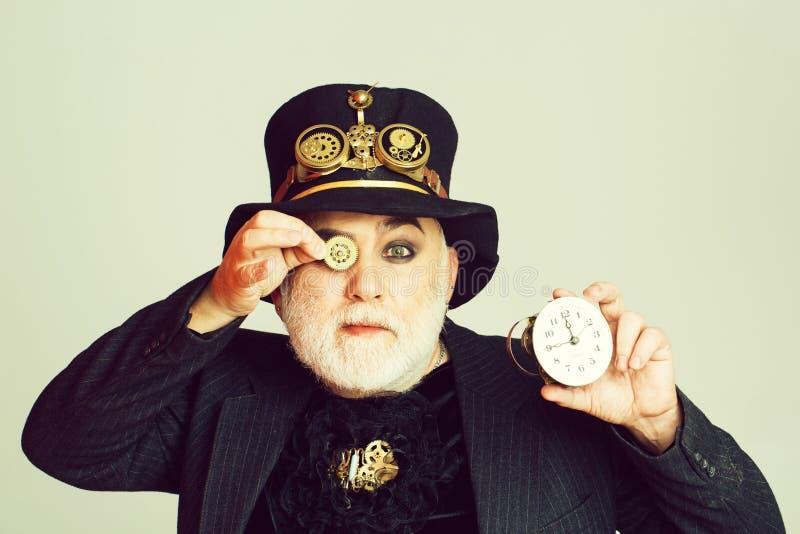 Человек держит cogwheel и часы стоковые изображения