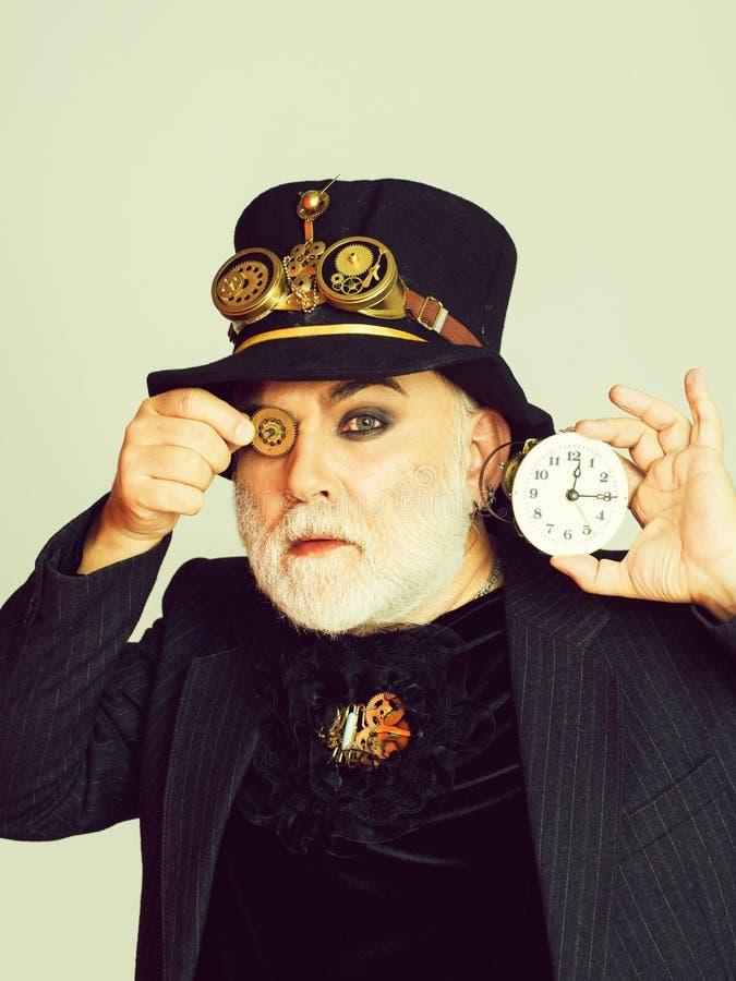 Человек держит cogwheel и часы стоковая фотография