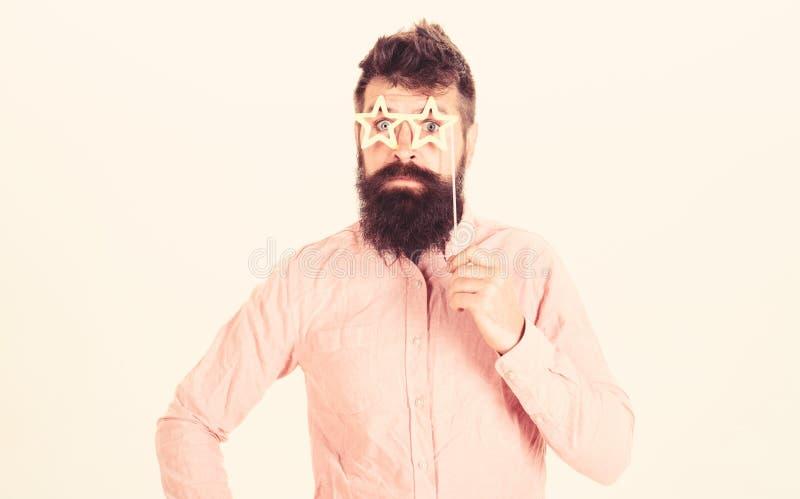 Человек держит eyeglasses упорок партии сформированные звездой, белую предпосылку Удивленный битник с бородой и усик на жизнерадо стоковые изображения