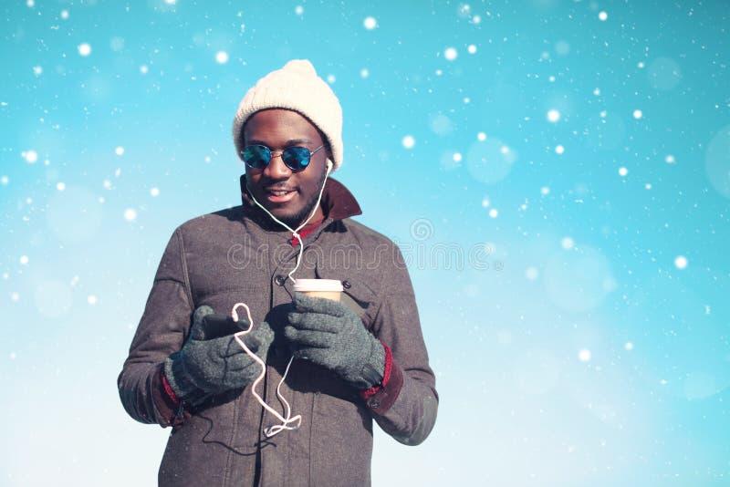 Человек детенышей портрета зимы усмехаясь африканский наслаждаясь слушая музыкой на smartphone стоковые фотографии rf