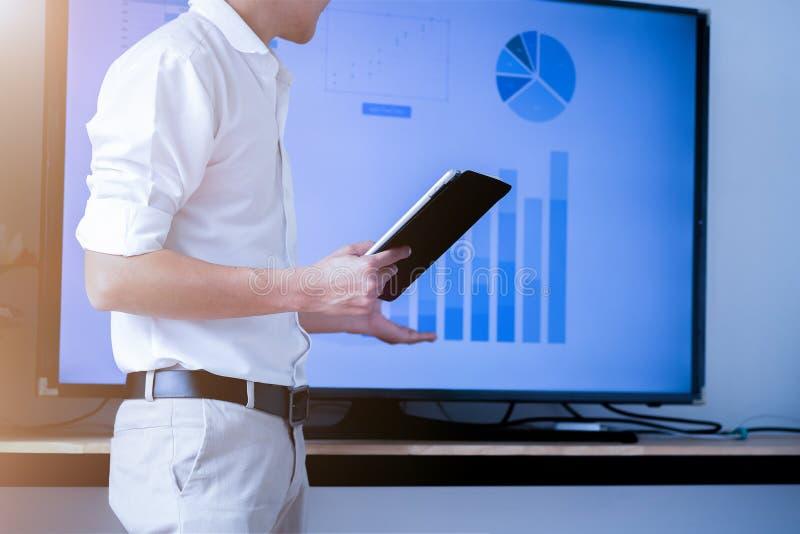 Человек диктора говоря с аудиторией давая лекцию и держа планшет Концепция представления дела стоковое изображение