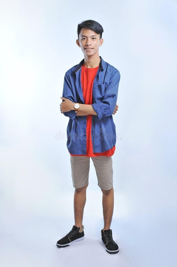 Человек доверия азиатский молодой нести случайные футболки с уверенный усмехаться стоковое фото