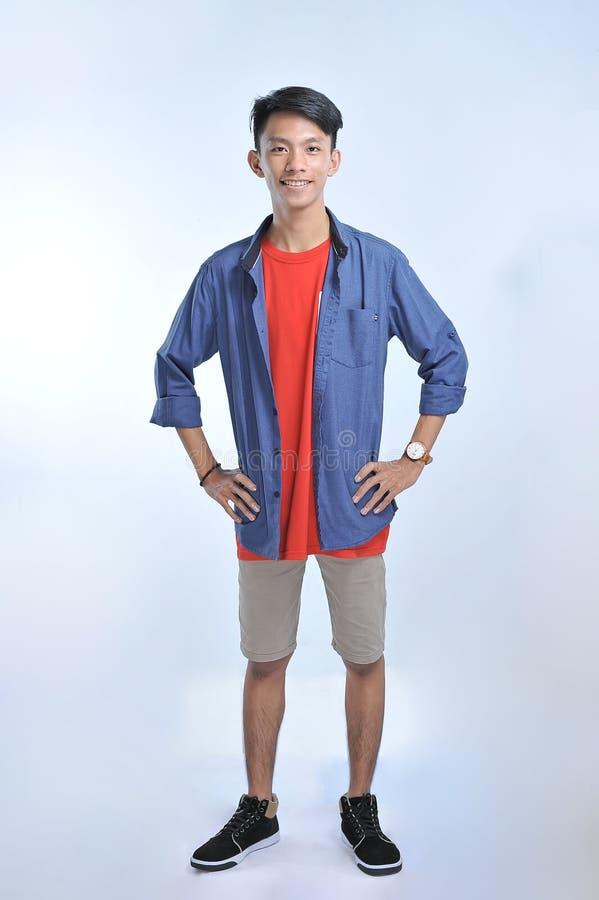 Человек доверия азиатский молодой нести случайные футболки с уверенный усмехаться стоковая фотография rf