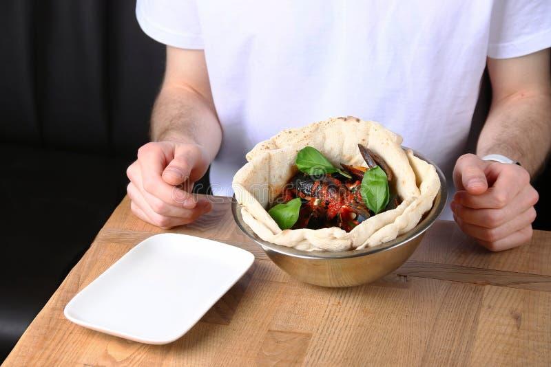 Человек есть в ресторане и блюдах на таблице стоковое фото rf