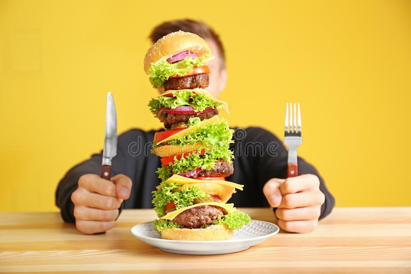 Человек есть огромный бургер на таблице стоковое изображение rf