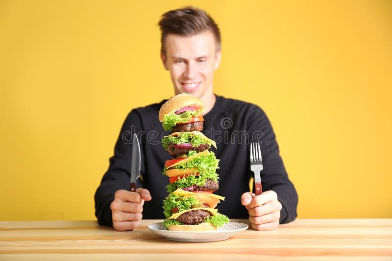 Человек есть огромный бургер на таблице стоковое фото rf