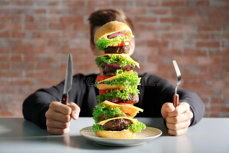 Человек есть огромный бургер на таблице стоковые изображения