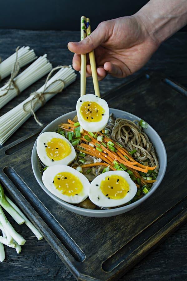 Человек ест лапши soba гречихи с соусом и гарниры в отваре Японская кухня Азиатская кухня Черная деревянная предпосылка Сторона стоковое фото