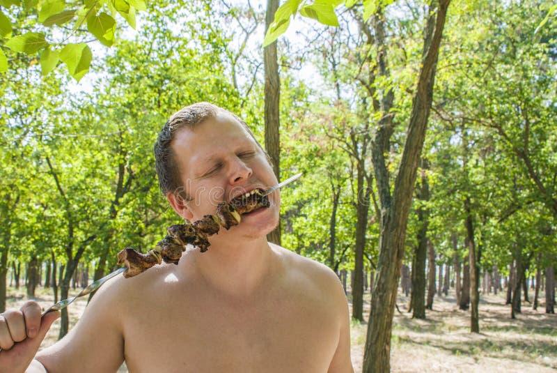 Человек ест shish kebab на протыкальниках стоковые фото