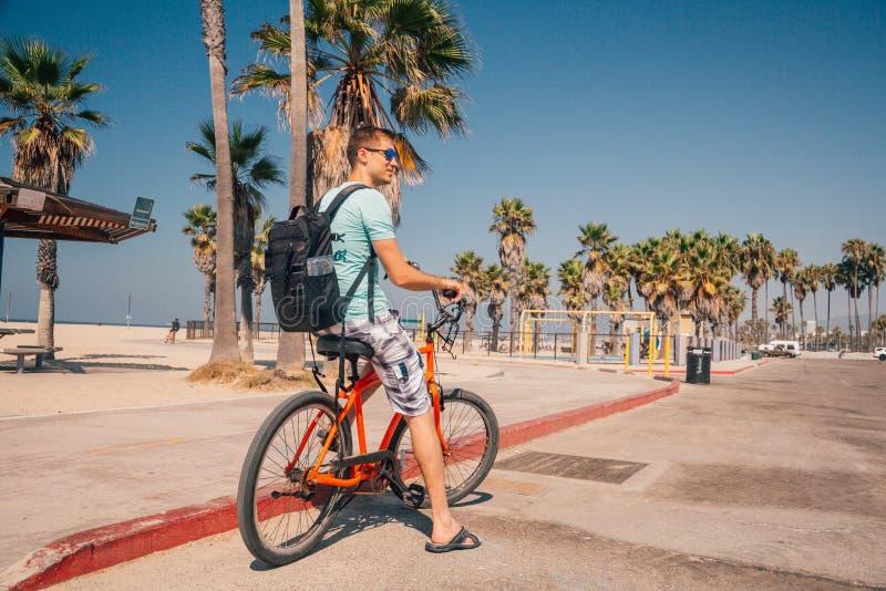 Человек ехать велосипед пляжа около пляжа Венеции в Лос-Анджелесе стоковые фотографии rf