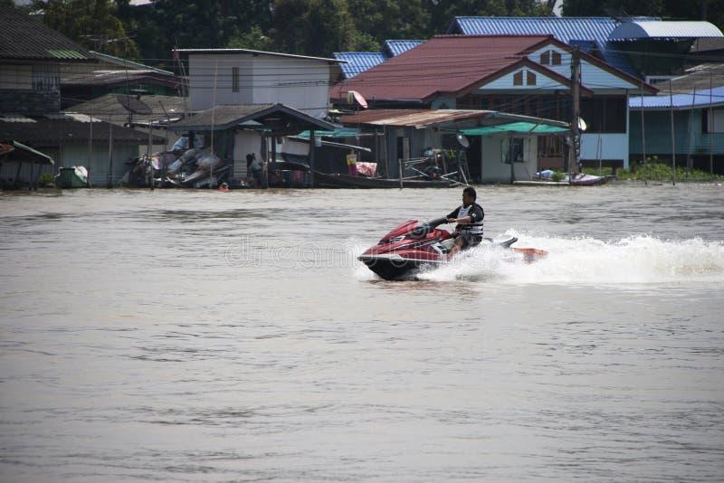 Человек ехать красная лыжа двигателя и выплеск мочат в центре реки стоковая фотография