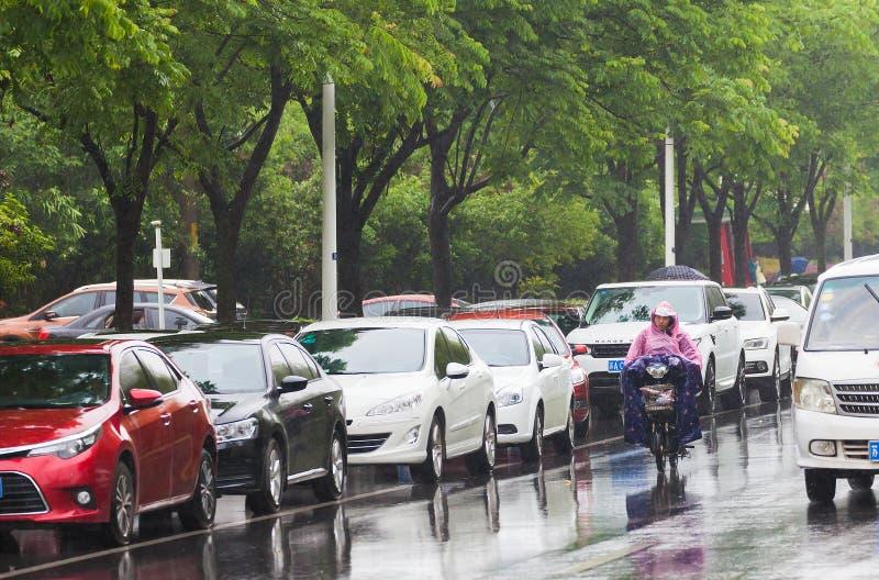 Человек ехать электрический велосипед в дожде стоковые изображения