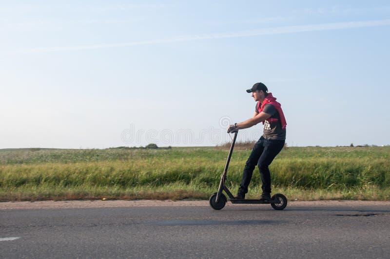 Человек ехать электрический самокат стоковые изображения rf