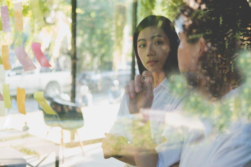 Человек & женщина обсуждая творческую идею с слипчивыми примечаниями на glas стоковые изображения rf
