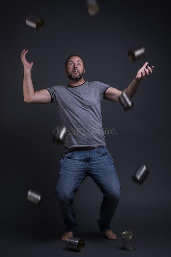 Человек жонглирует с пустыми чонсервными банками стоковые изображения rf