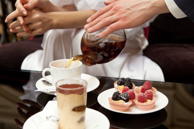 Человек заботит для женщины: льет ее зеленый чай На таблице десерты: тирамису и печенья со свежими ягодами Без сторон стоковое фото