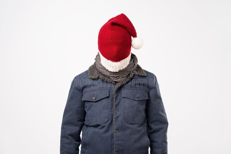 Человек закрывает его сторону с крышкой рождества красной пробуя остаться anonym стоковая фотография rf