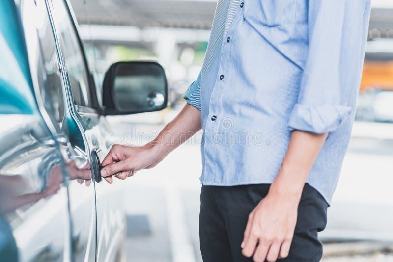 Человек запирая вверх или открывая автомобильную дверь с ключом стоковые фото