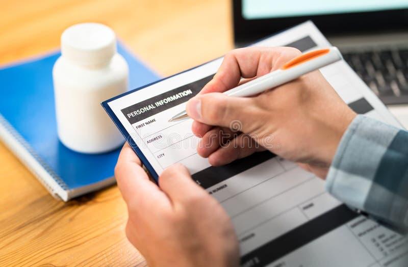 Человек заполняя медицинскую форму для медицинской страховки Исследование медицины стоковые фото
