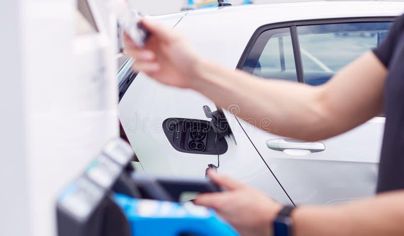 Человек, Зарядящий Электромобиль, Платит За Энергию С Кредитной Картой На Зарядной Станции стоковые изображения rf