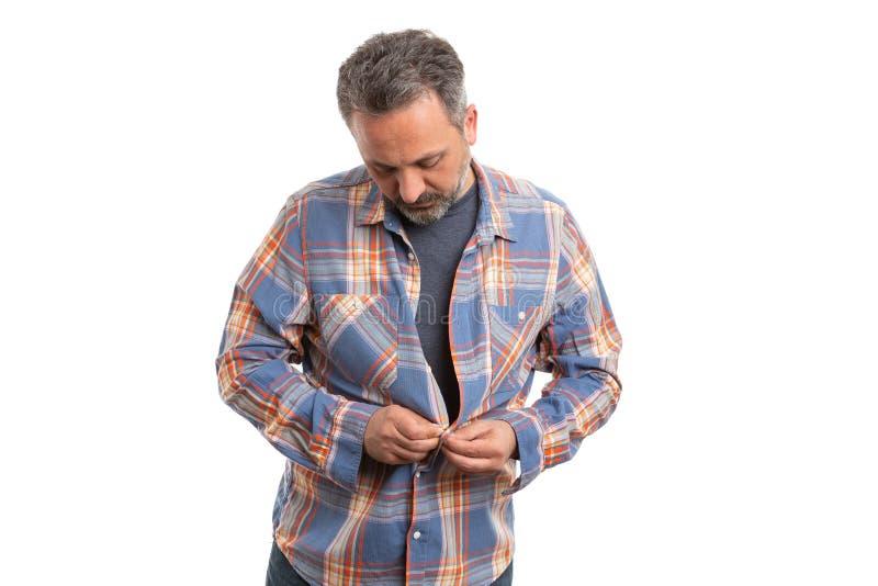 Человек застегивая вверх по рубашке стоковое фото