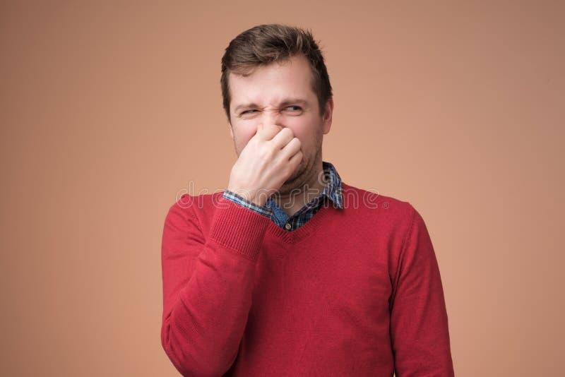 Человек затыкает нос как запахи что-то вонь стоковая фотография
