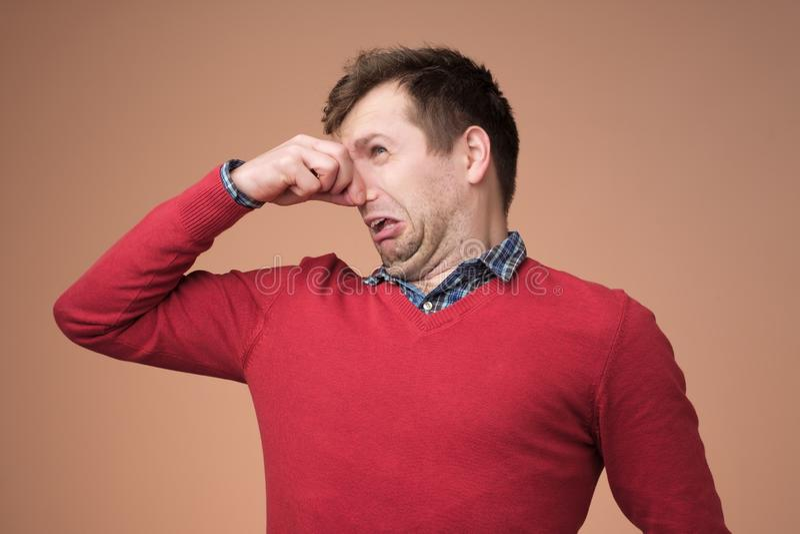 Человек затыкает нос как запахи что-то вонь стоковое изображение