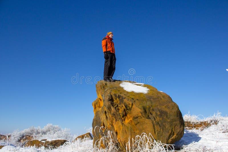 Человек зимой на скале, зимой в горах на стеклянном оранжевом - молодой человек стоковое фото