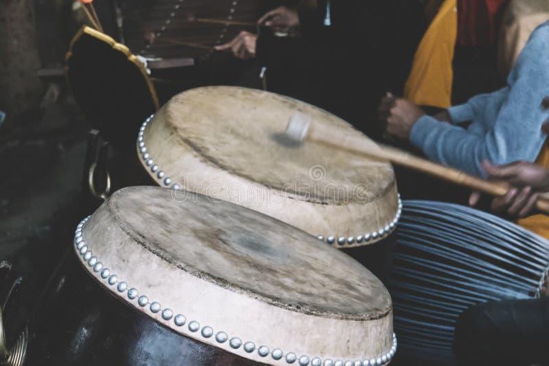 человек играет барабанчик тенет в предпосылке нижнего света стоковая фотография rf