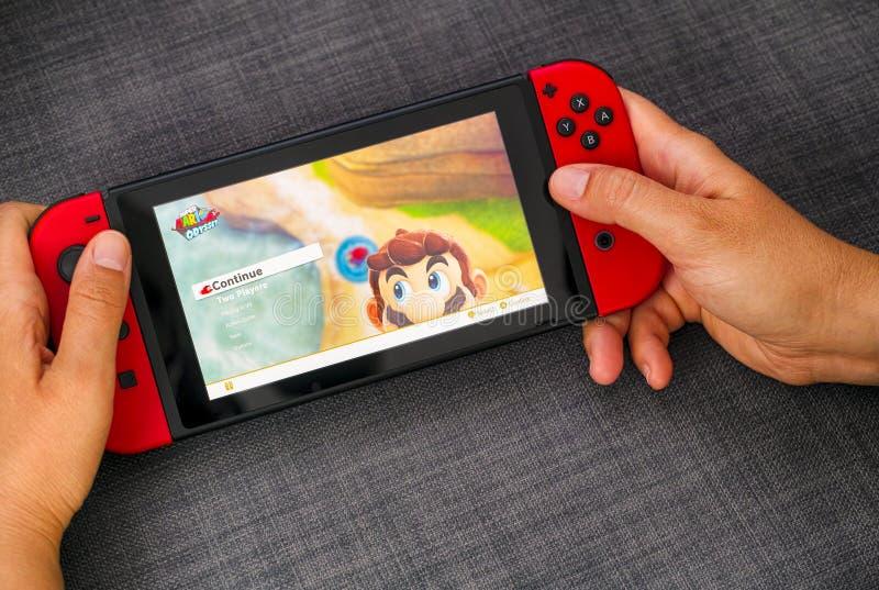 Человек играет в супер-Mario Maker 2 в видеоигре на консоли Nintendo Switch стоковое фото rf